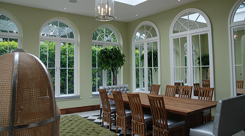 Newly renovated interior by architects in Berkshire, large dining room, large full height windows to the outside to allow light into the room, with large mirrored windows on the wall to give the effect of being in the center.