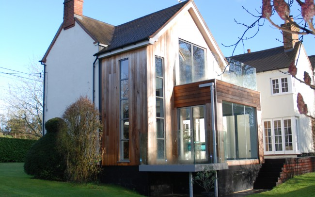 View of completed project, designed by Inspiration Architects, large areas of glazing allow undisturbed views over the water and fold back glazed walls allow free flow of space between the new kitchen dining area and the new raised terrace decking.