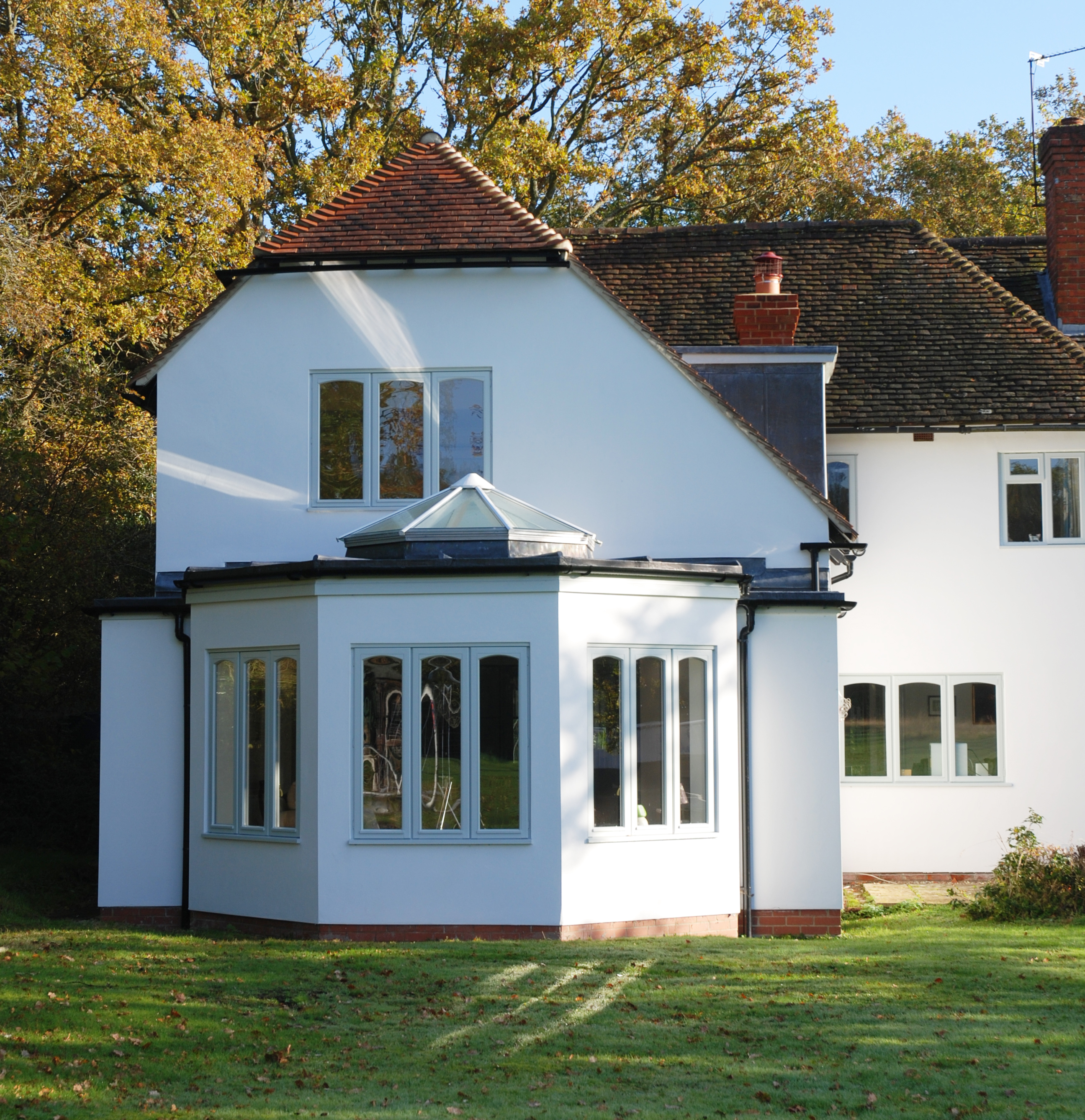 Home extensions design by Inspiration Architects. An extension was added to the front creating a large hall space with an open fire, and is orientated such that full views of the grounds to the rear of the house are revealed.