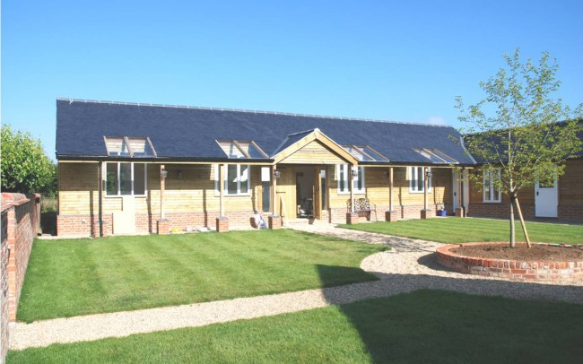 Home architecture in Newbury by Inspiration Architects, new outbuildings with wooden frontage and slate roofing.