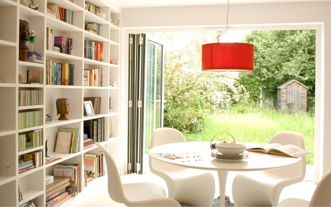 New house architecture by Inspiration Architects. Dining room with view to the back garden. Left wall is a complete shelving unit, with white furniture and carpet for a modern design.