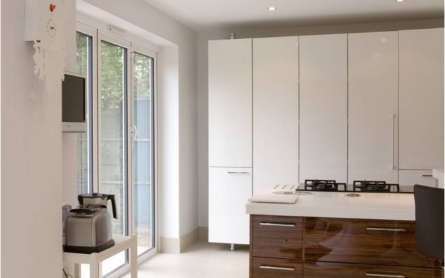 Beautifully designed white kitchen, with simple white gloss furniture on wood. New house architecture by Inspiration Architects.