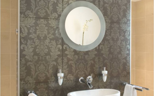 Bathroom inside the new house architecture project by Inspiration Architects. Beige tiles, a feature wall with a decorative pattern and white basins and furniture.