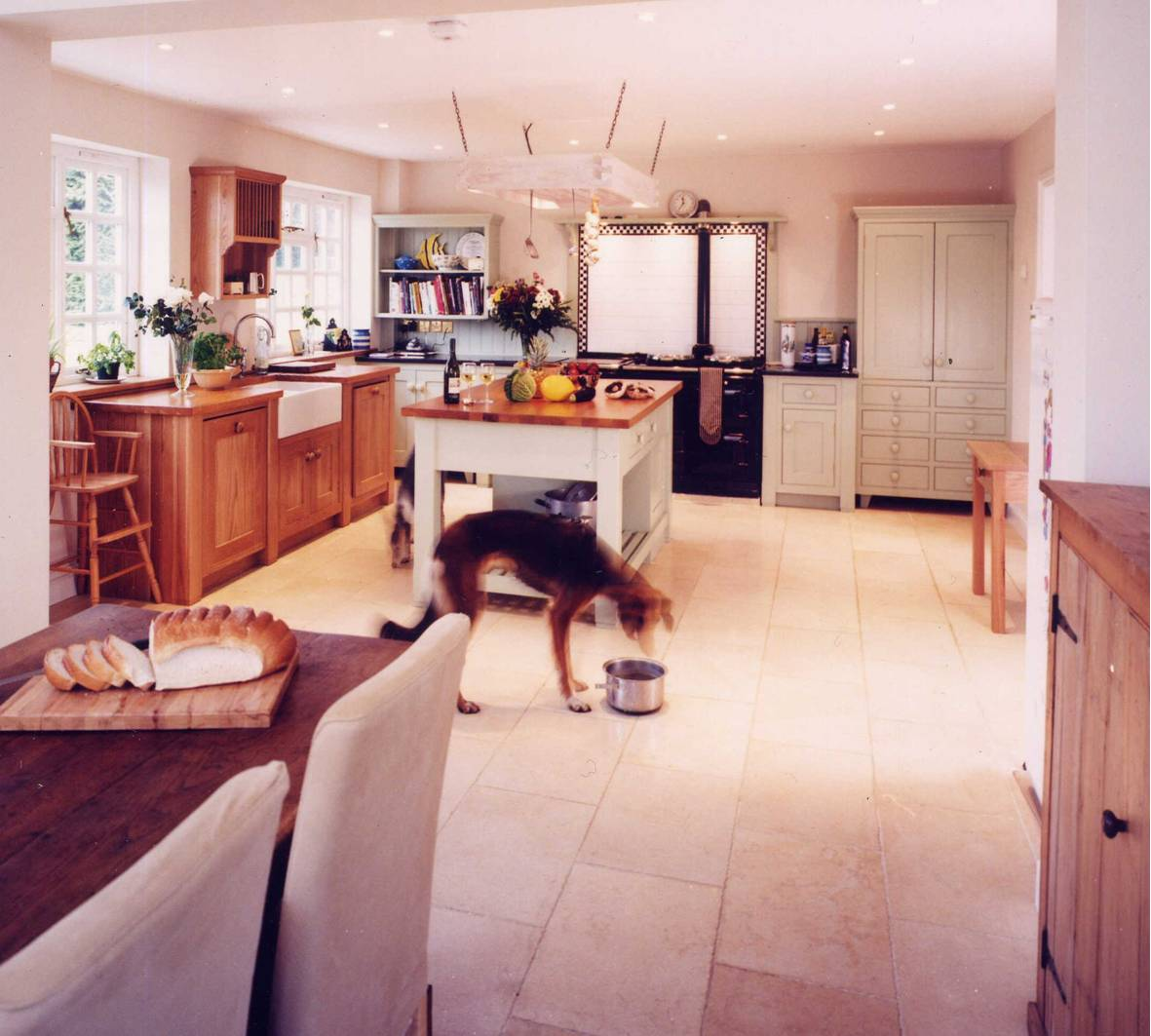 Dog eating from a bowl in the middle of a newly redmodeled kitchen. Architects near me, Inspiration Architects, were able to create a a very modern, cream with wood finish kitchen.