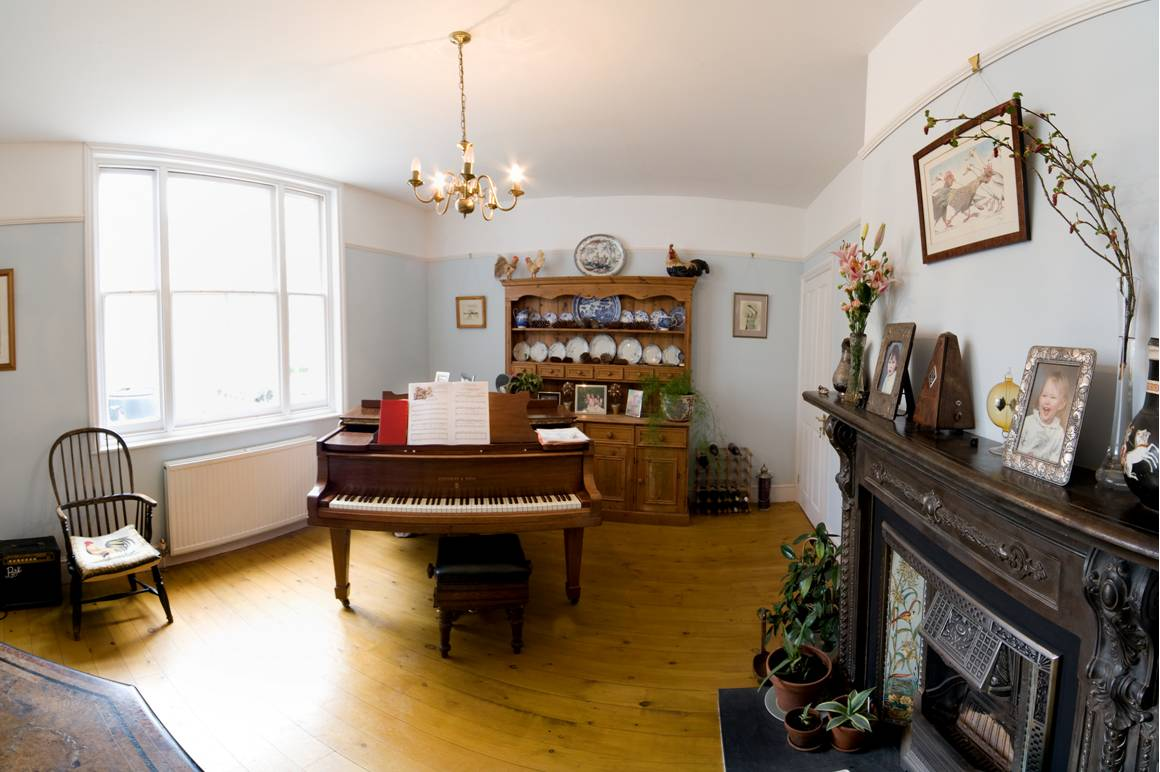 Piano room of newly remodelled home. Light wooden flooring with large windows to allow light to reflect throughout the room. Grand piano at the center. Here you will find an architect who can do the same for you.