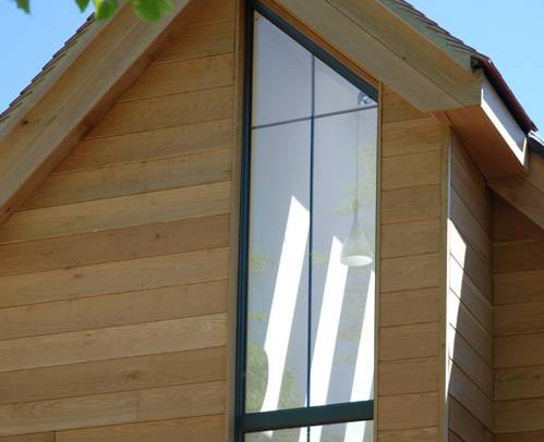 Inspiration Architects in Hampshire, new build eco home exterior, wood on white design, ceiling is lined with skylights to ensure a bright welcoming feel.