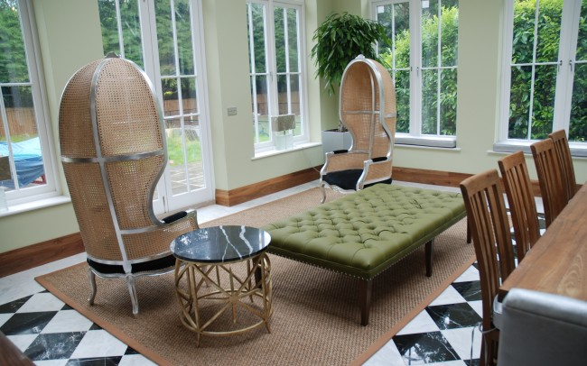 Interior remodeling in Ascot, design my home with Inspiration Architects. Interior view of dinning area. Metal framed chairs with weaved backings around a plush green footstool/table, surrounded by light and windows