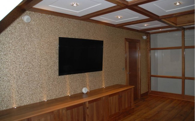 Design my home with Inspiration Architects. Interior of room. Wooden Laminated flooring, feature wall with small stones, widescreen TV mounted to wall, with white inset ceiling lights.