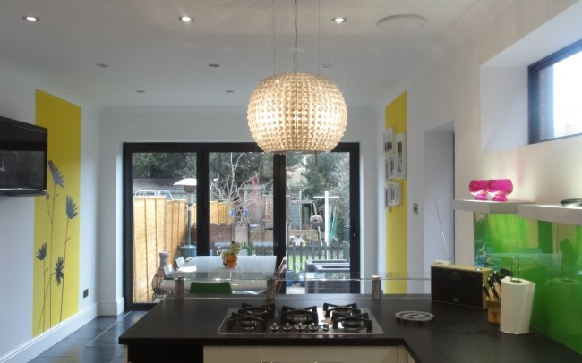 View from kitchen to the door. Interior architecture remodeling in Newbury by Inspiration Architects. Modern kitchen designed to let in maximum light, with granite worktops, pale wood finished cabinets and grey tiled flooring.